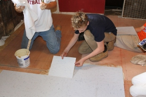 Sam M. placing floor tiles.